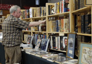 A customer peruses one exhibitor's inventory at last year's Rochester Antiquarian Book Fair