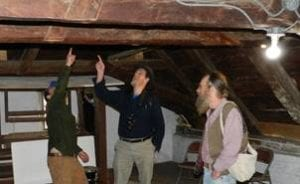 Members of the Traditional Timber Frame Research and Advisory Group examine timber framing in the attic of the Jean Hasbrouck House,