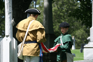 Re-enactors conduct the flag switching ceremony during an Independence Day observance