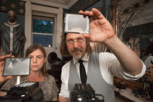 Joel Schlemowitz and his partner Dawn Elliott examine magic lantern slides