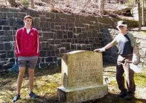Saranac Lake High School student James and Gary Baldwin stand with the gravestone of Dr Edward and Mary Baldwin